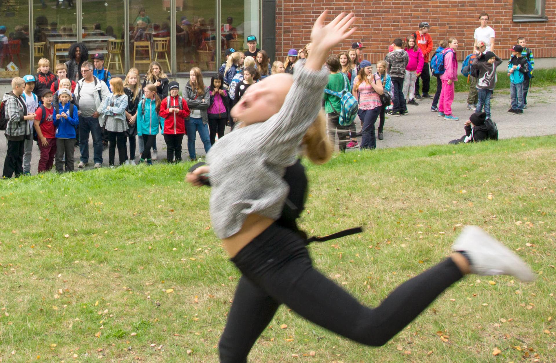 Flicka hoppar framför en samling barn